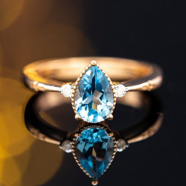 A delicately tapered 14k rose gold band with a pear cut sky blue topaz center stone.