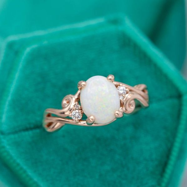 An oval Australian white opal set in a curving rose gold engagement ring.