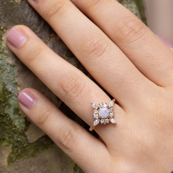 There's plenty of diamond sparkle around the Northern Lights coloration of this engagement ring's opal center stone.