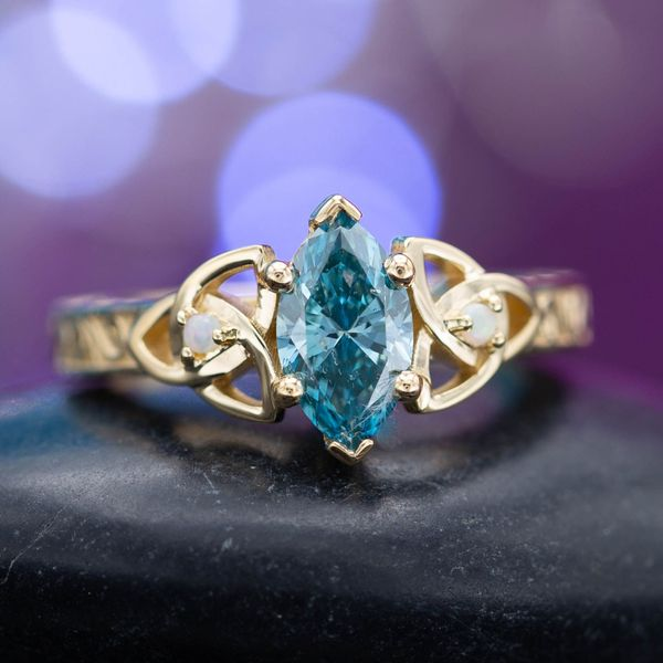 A 1.02ct fancy blue diamond, marquise cut, set in a Celtic-inspired ring with trinity knots and opal accents.