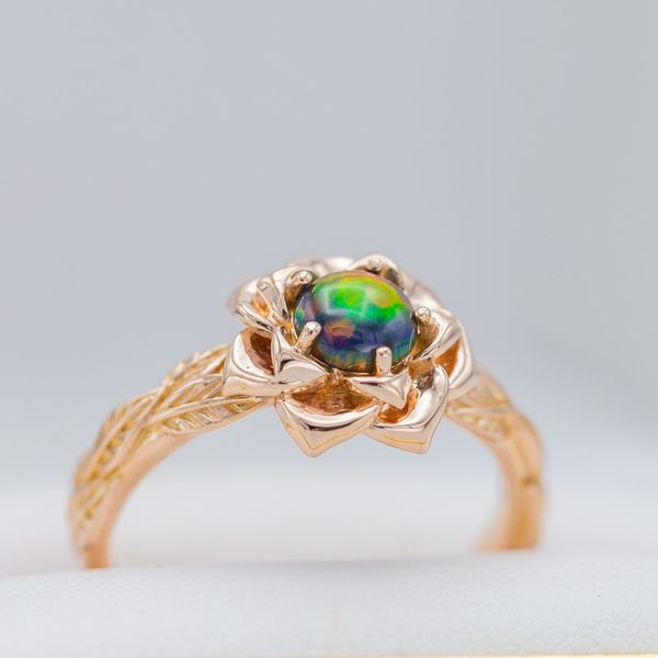 The lab-created black opal at the heart of this rose ring shows intense color play.