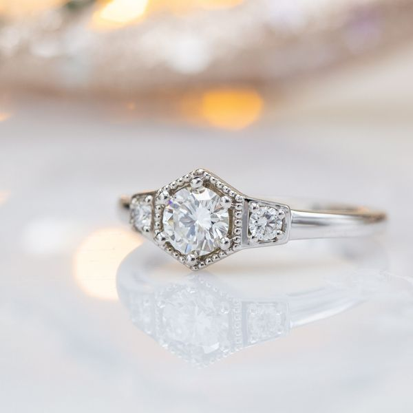 Deco-inspired hexagon setting for a half-carat round diamond center stone with bead detailing.
