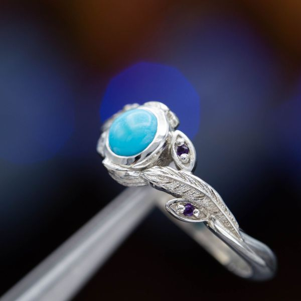 Feathers and amethysts pair perfectly with a clean blue turquoise in this engagement ring.