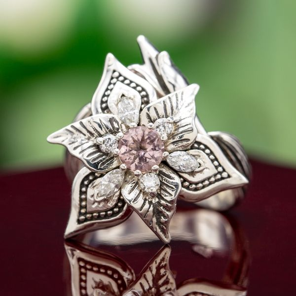 A bold, sculptural lily ring with morganite and diamond accents. The vining band tucks a bud under the blooming center setting.