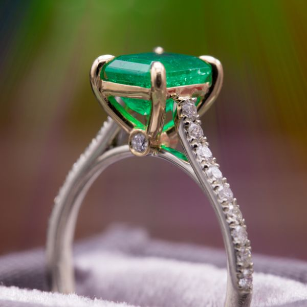 Mixed yellow and white gold and pave diamonds create a perfectly delicate ring with just a nod toward vintage inspiration in the claw prongs that hold the stunning 1.35ct emerald cut emerald.