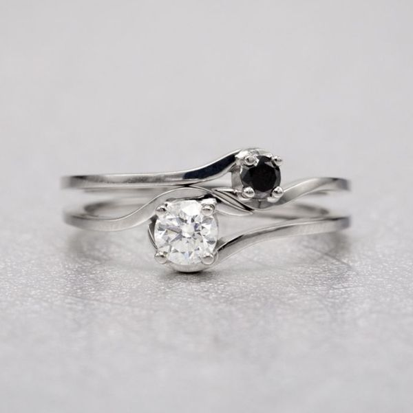 Yin-and-yang inspired ring set with black and white diamonds in balance when the bridal set is worn together.