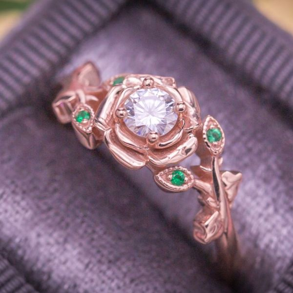 Softly curving rose gold rose petals frame the moissanite center stone, with pops of emerald accenting the leafy shank.