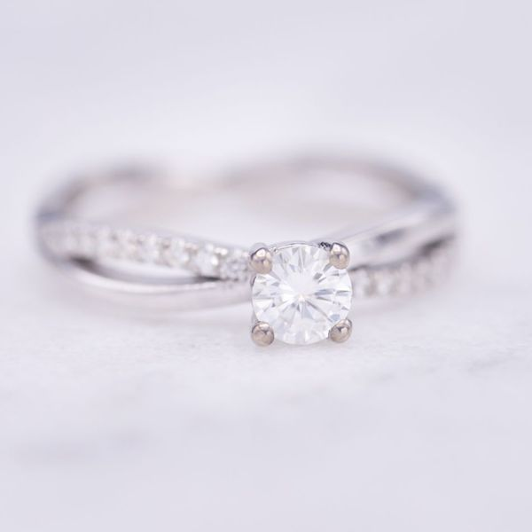 Delicate twisted white gold band setting for a moissanite center stone.