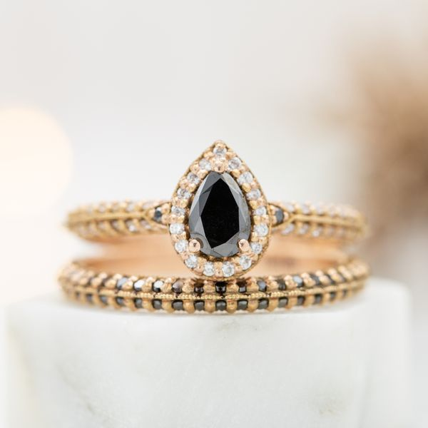 This natural diamond was color enhanced to bring out to bring out a perfect black color. It's set in a bridal set with a halo and two rows of diamonds on the bands.