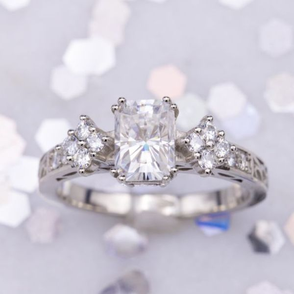 A radiant cut center stone surrounded by round accents set in a diamond shape.