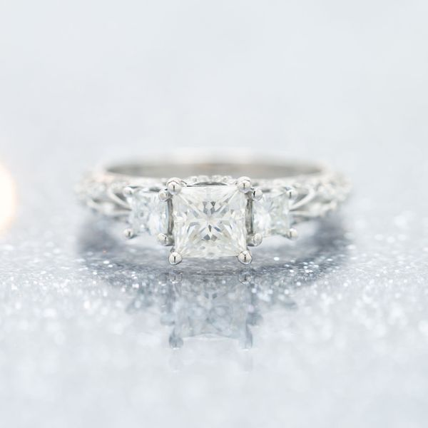 Three-stone setting of princess cut moissanites on an ethereal filigree band.