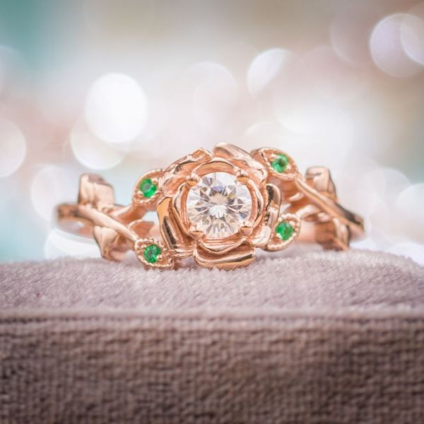 A sparkly moissanite nestles in the rose gold petals of this rose setting, with emeralds adding color to the leafy shank.