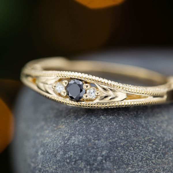 A delicate yellow gold band features a center setting of black diamond to create an understated look.