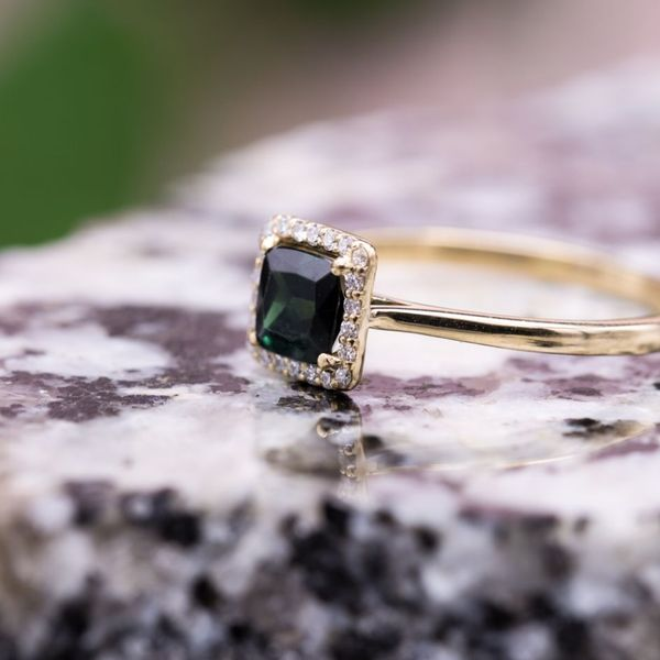 A rich, green cushion cut green tourmaline sits in a floating diamond halo in this classic gold ring.