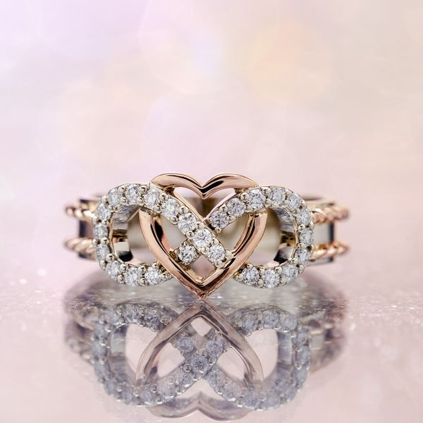 A unique engagement ring with heart and infinity symbol in mixed rose gold and white gold.