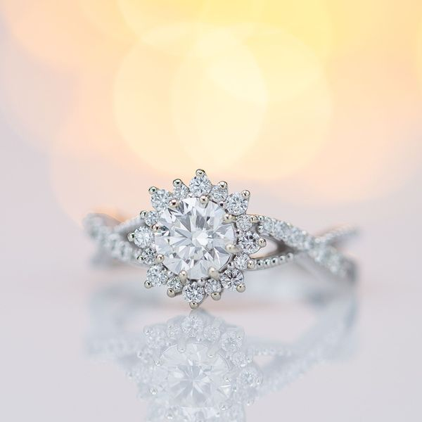 A vining band and delicate sunburst halo accentuate the perfect hearts & arrows diamond in this engagement ring.