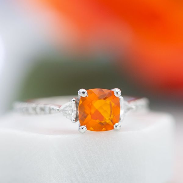 The vivid, fiery red of this fire opal draws the eye as the center stone of a contemporary, three-stone engagement ring.