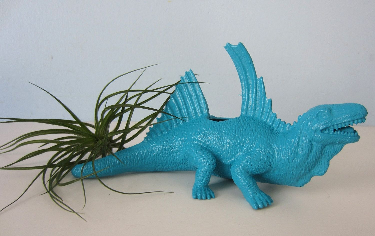 Hand Refinished Repurposed Toy Dinosaur Planter comes with a small air plant.