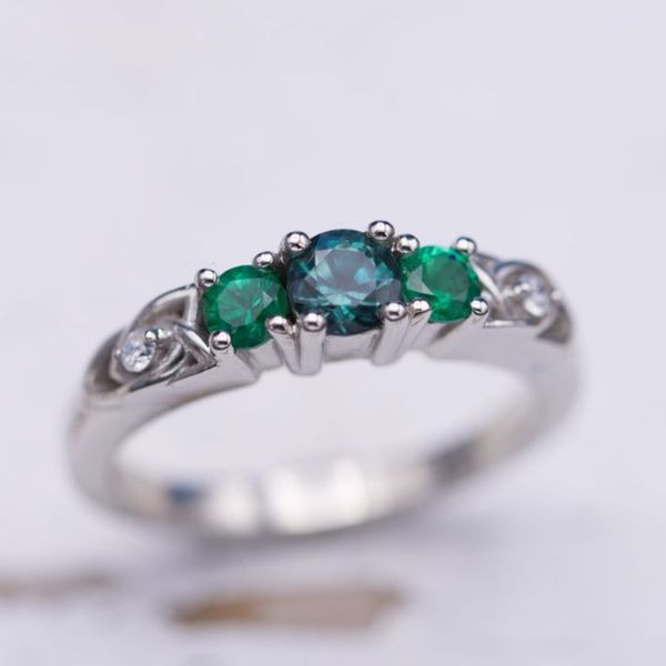3-Stone engagement ring with emeralds and alexandrite and trinity knot accents.