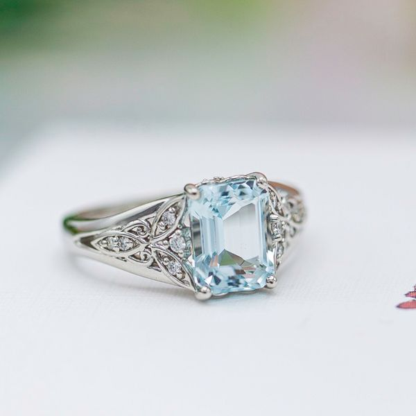 Vintage-inspired engagement ring with emerald cut aquamarine and open shoulder details hinting at a dragonfly.