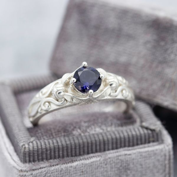 An iolite engagement ring with ornate detailing on the band framing the dark purple-blue center stone.