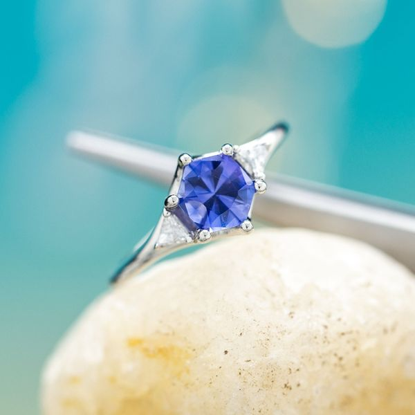 Beautifully geometric hexagon cut blue sapphire pairs with a softly tapered white gold band.