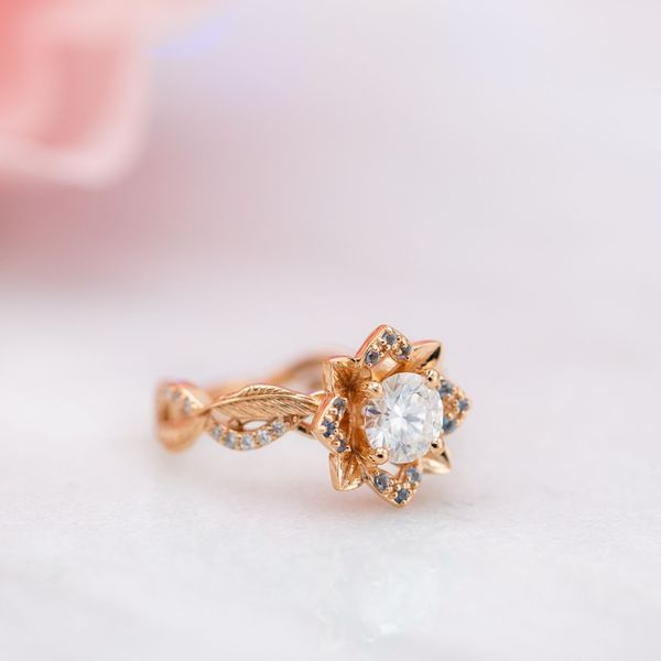 Rose gold and moissanite lotus engagement ring with quills along the band and aquamarine accents.