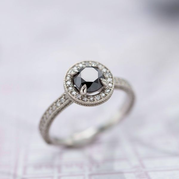 Halo engagement ring with black diamond and milgrain-lined channels.