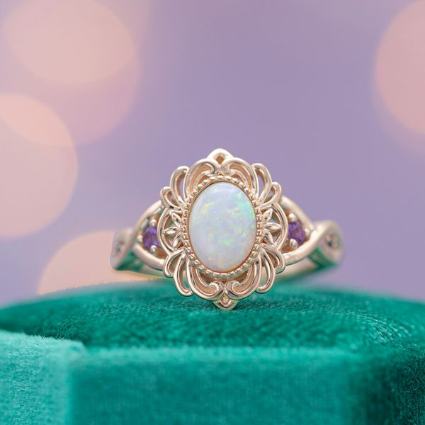 A frame of intricate rose gold wirework creates a faux-halo around this ring's opal center stone.
