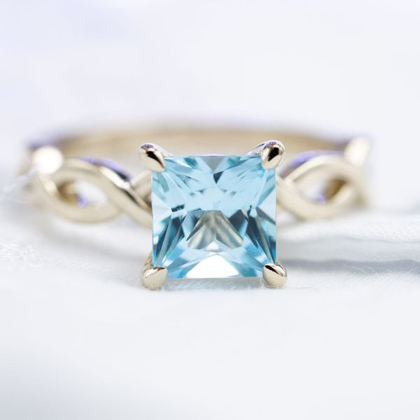A crystal clear princess cut sky blue topaz set in a delicately vining 14k white gold shank.