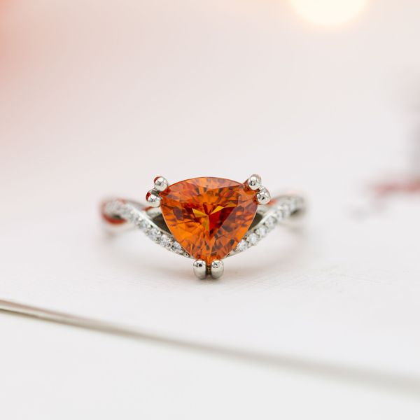An incredible, vivid orange sapphire engagement ring with a delicate, twisting band with diamond pave.