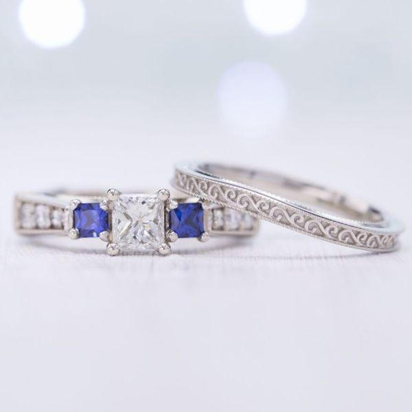 Bridal set featuring princess cut diamond and side sapphires, milgrain detailing, and beautiful scrollwork on the wedding band. Personal touches (a globe and a ballet slipper) are sculpted on the sides of the setting to reflect the couple.