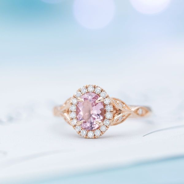 This pink oval morganite is set in rose gold with a diamond halo and a milgrain band.