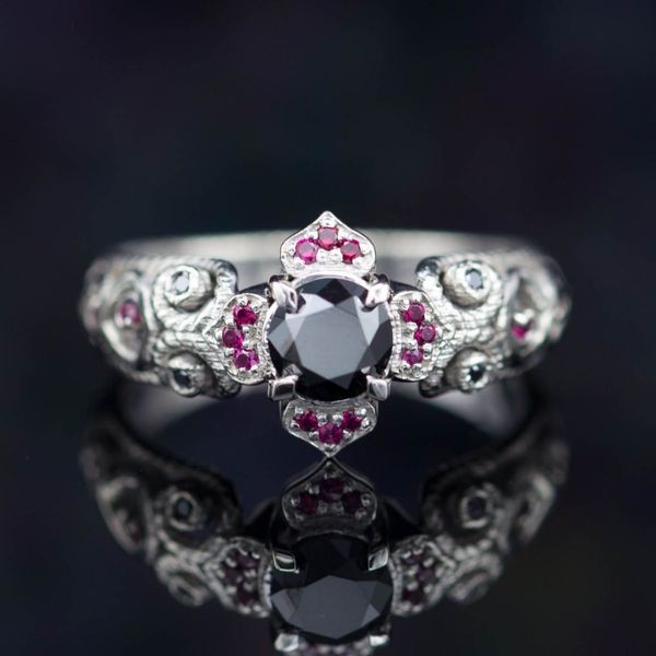 A stunning black diamond ring with gothic styling, surrounding the center stone with ruby accents and rope-textured scroll details.