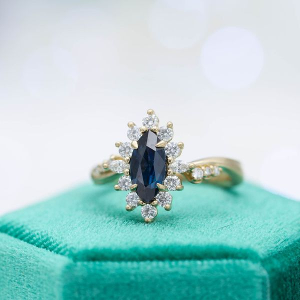 We designed this vintage-inspired engagement ring with a sunburst halo around an inky, midnight blue sapphire.