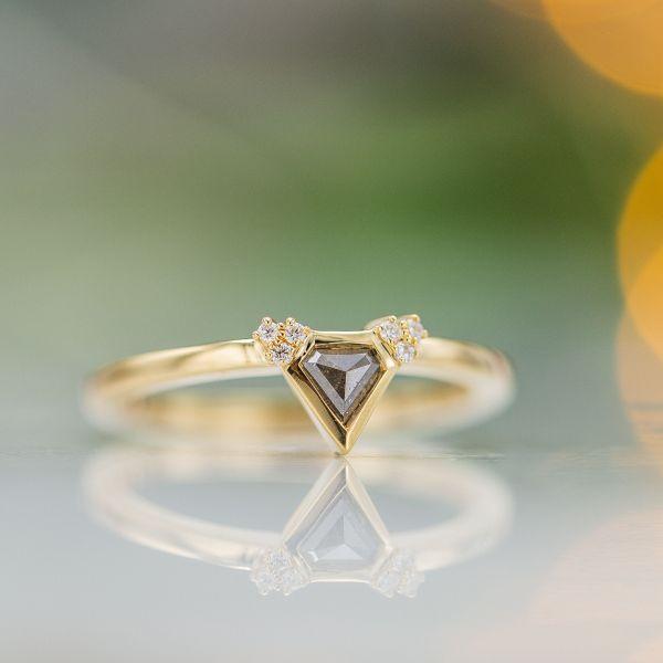 A perfectly modern, ultra delicate ring showcasing a pentagon cut salt & pepper diamond.