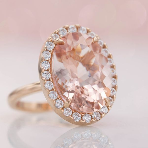 This huge, gorgeous center stone is a nearly 12 carat oval morganite, but the clarity of the gem and the delicate halo keep the setting feeling light.