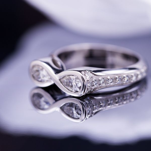 Infinity setting of two pear cut moissanite gems, with moissanite accent gems lining the white gold shank.