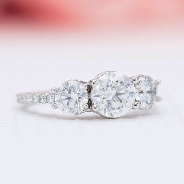 A delicate 14K white gold band with intricate setting detailing, holding a center 0.87ct lab-created diamond nestled between two 0.39ct lab-created diamonds.