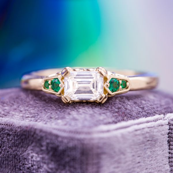 An east-west set emerald cut diamond surrounded by kite shaped features with emerald accents.