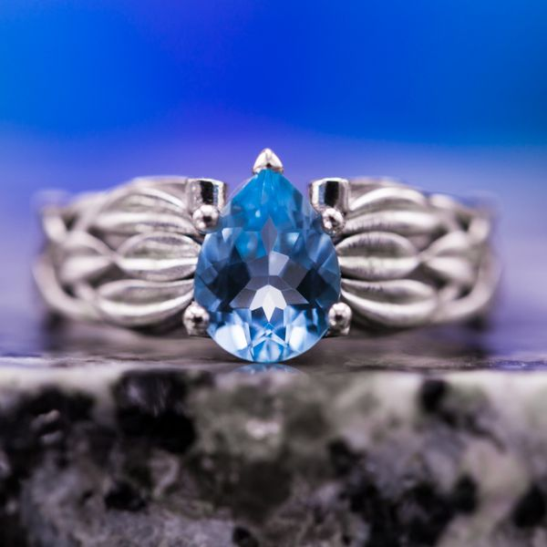 Pear cut sky blue topaz set in a white gold shank with layered leaf detailing.
