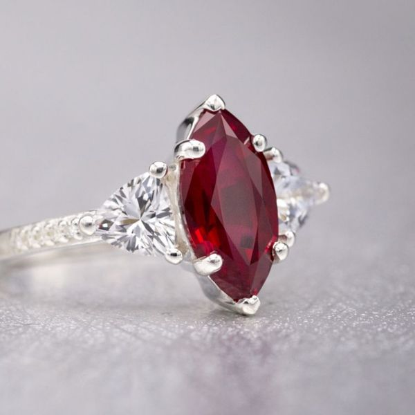 A rich red marquise cut ruby pairs with trillion cut white sapphires a moissanite pave on the delicate band.