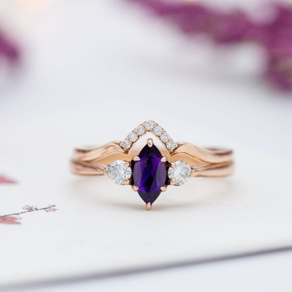 A deep purple amethyst pairs with diamonds in a three stone engagement, and a matching wedding band adds sparkle.