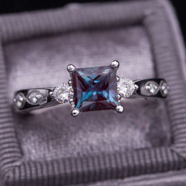 White gold engagement ring with princess cut alexandrite and moissanite side stones.