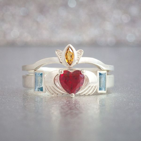 A classic claddagh bridal set design with a ruby for the center heart, surrounding it with citrine and aquamarine accents.