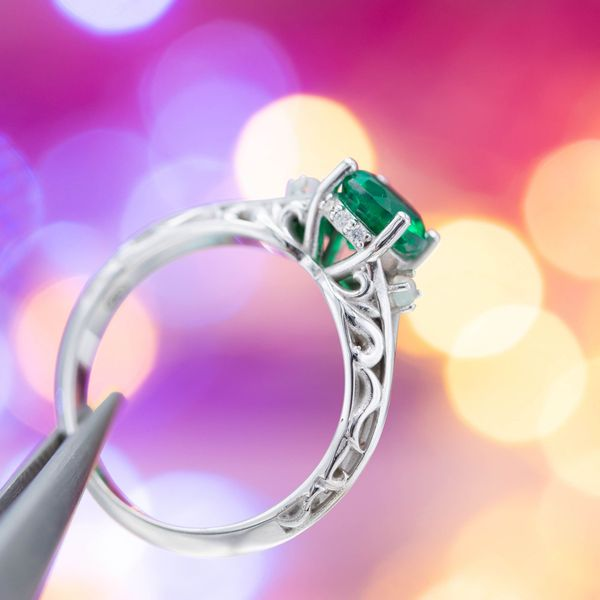 Scroll details and diamond accents frame the round emerald center stone, and two small opal birthstones are set on the shoulder.