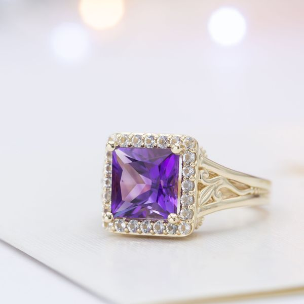 A bold amethyst engagement ring with a princess cut center stone, halo, and vine detailing.