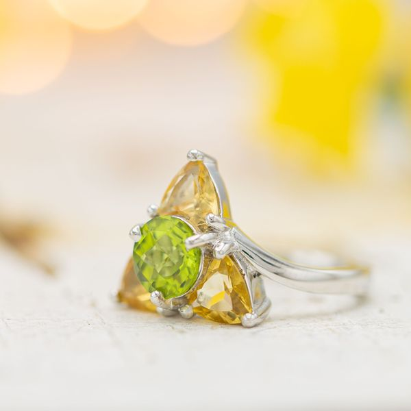 Triforce-inspired engagement ring with peridot and imperial topaz.