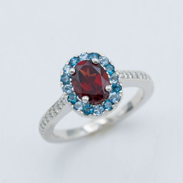 Diamonds make an appearance in this halo ring, but the center setting is all bright gemstones: garnet surrounded by aquamarine and topaz.