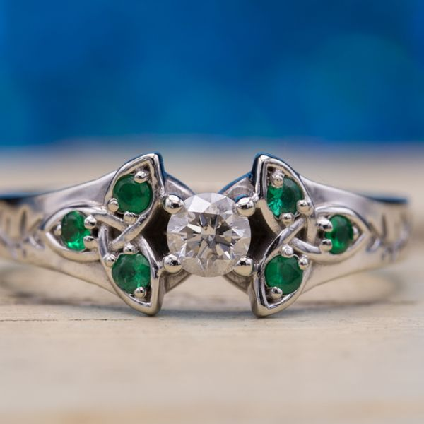 Emeralds accent the trinity knot shank, bringing together the Celtic and natural themes in this engagement ring. We opted for a smaller center diamond with a very low profile to make sure this ring could be easily worn even when she's working with her hands.